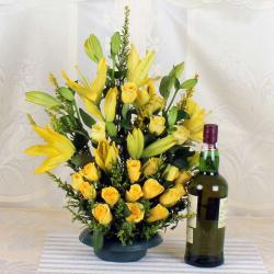 Arrangement of Yellow lilies and Roses with Bottle of Wine